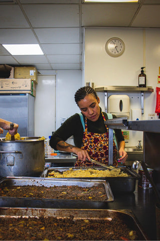 Gemma working away in the Plant Stories kitchen; her hair in beautiful braids, and wearing a vibrant floral apron in oranges, reds, pinks, and greens. She is preparing a huge tray of delicious self-serve food. In front of her sit two (equally huge) metal trays of bean stew, ready and waiting to be eaten!
