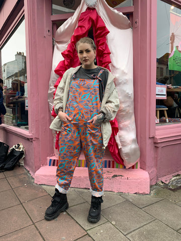 One of our beloved Brighton customers wearing their vulva print dungas with pride, outside our first Brighton store - the doorway is draped in a giant fabric vulva, obviously!