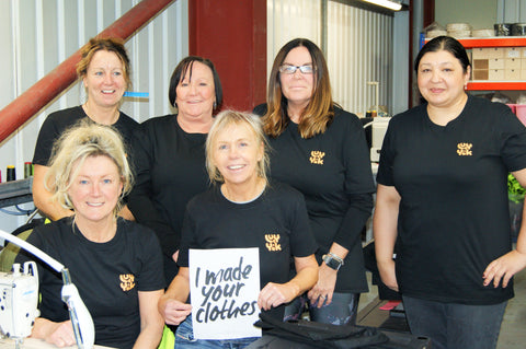 """Our Made in Britain seamstresses pose together in their sewing room, holding a sign saying """"I made your clothes"""". The team wear matching black t-shirts accented with our iconic Lucy & Yak logo."""