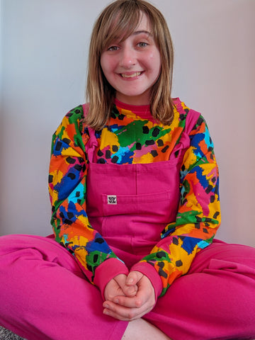 A photo of an Autistic person sitting crossed legged with their hands in their lap. They are wearing a multicoloured Sonny top and bright pink Atlas dungarees.