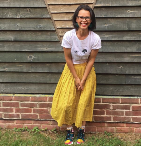 Jamie the Unwedding Wedding Expert, smiling by a barn in a yellow dress, white top and fun colourful trainers
