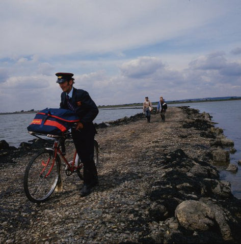 Postman Ken Chaplin pushing his bicycle across a causeway