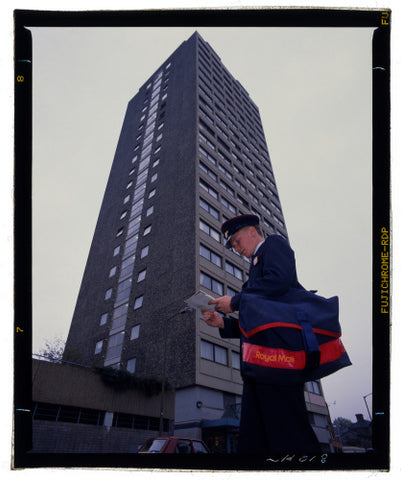 Postman Jamie Long sorts out his delivery to flats in Battersea, London, c.1988-1989