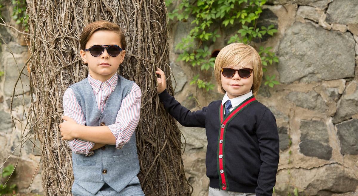 two stylish preppy boys posing outside with polarized colored tortoise wayfarer and aviator style sunglasses