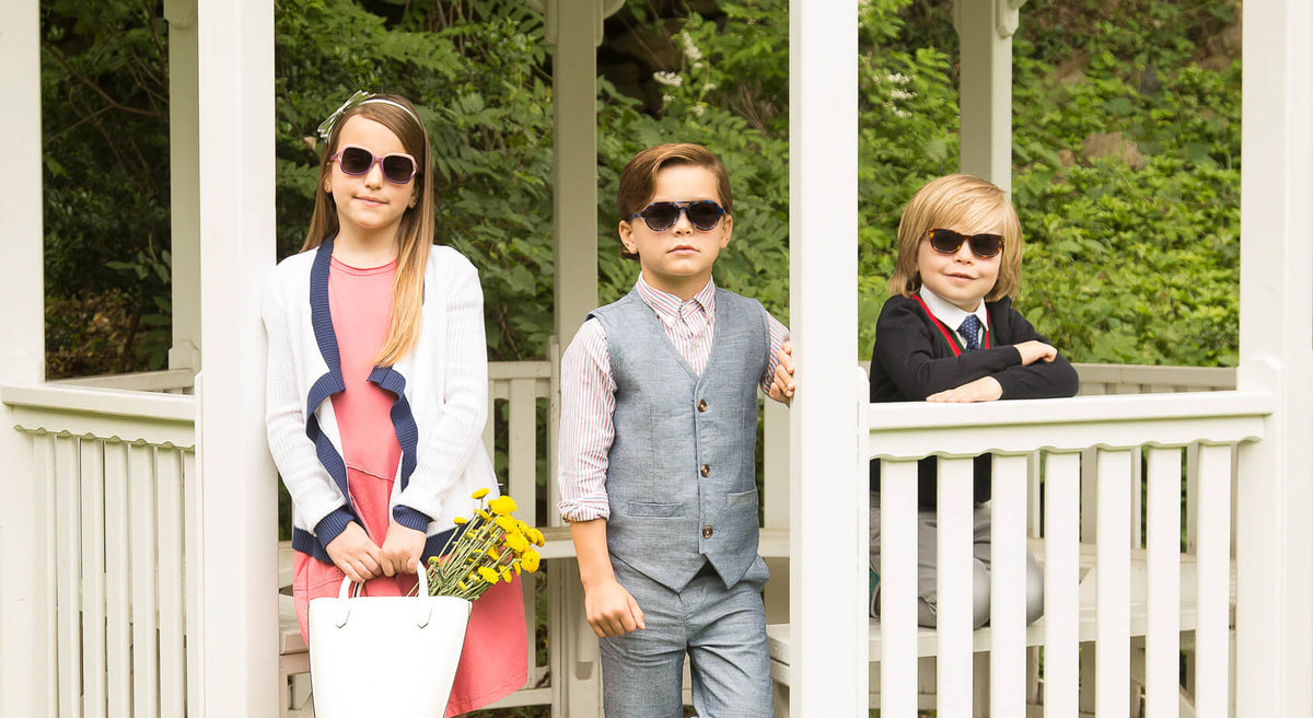 2 boy and 1 girl adorably dressed posing together looking chic wearing properly sized polarized sunglasses for kids