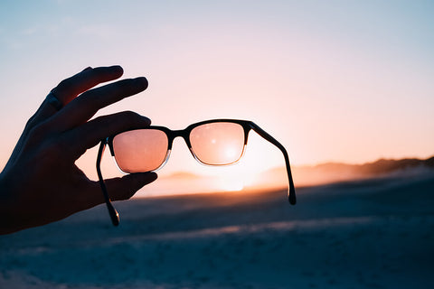 man holding sunglasses up to sunset to look at the tint of the lens