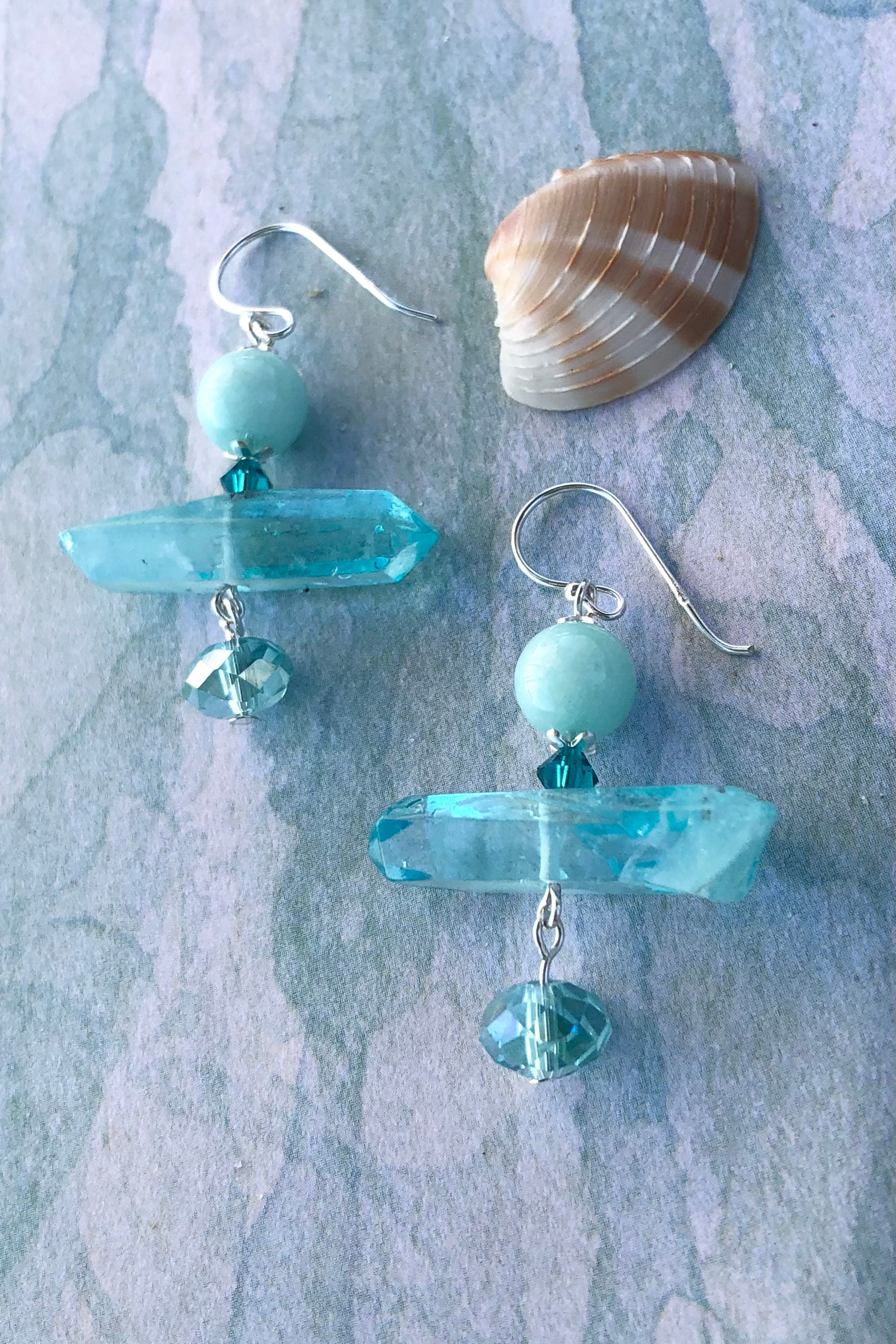 A drop design, with the sparkle of pale aqua crystal trembling at the base.