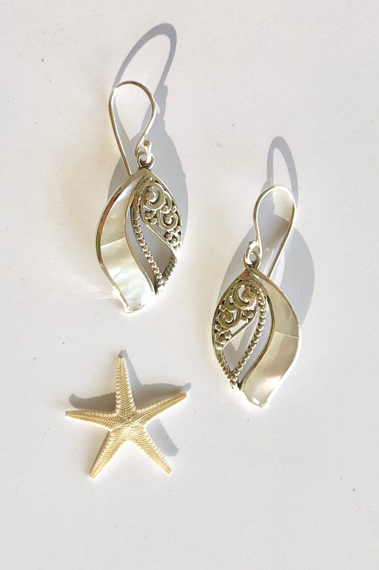 drop earrings with a 925 solid silver wave design over an iridescent Mother of Pearl.