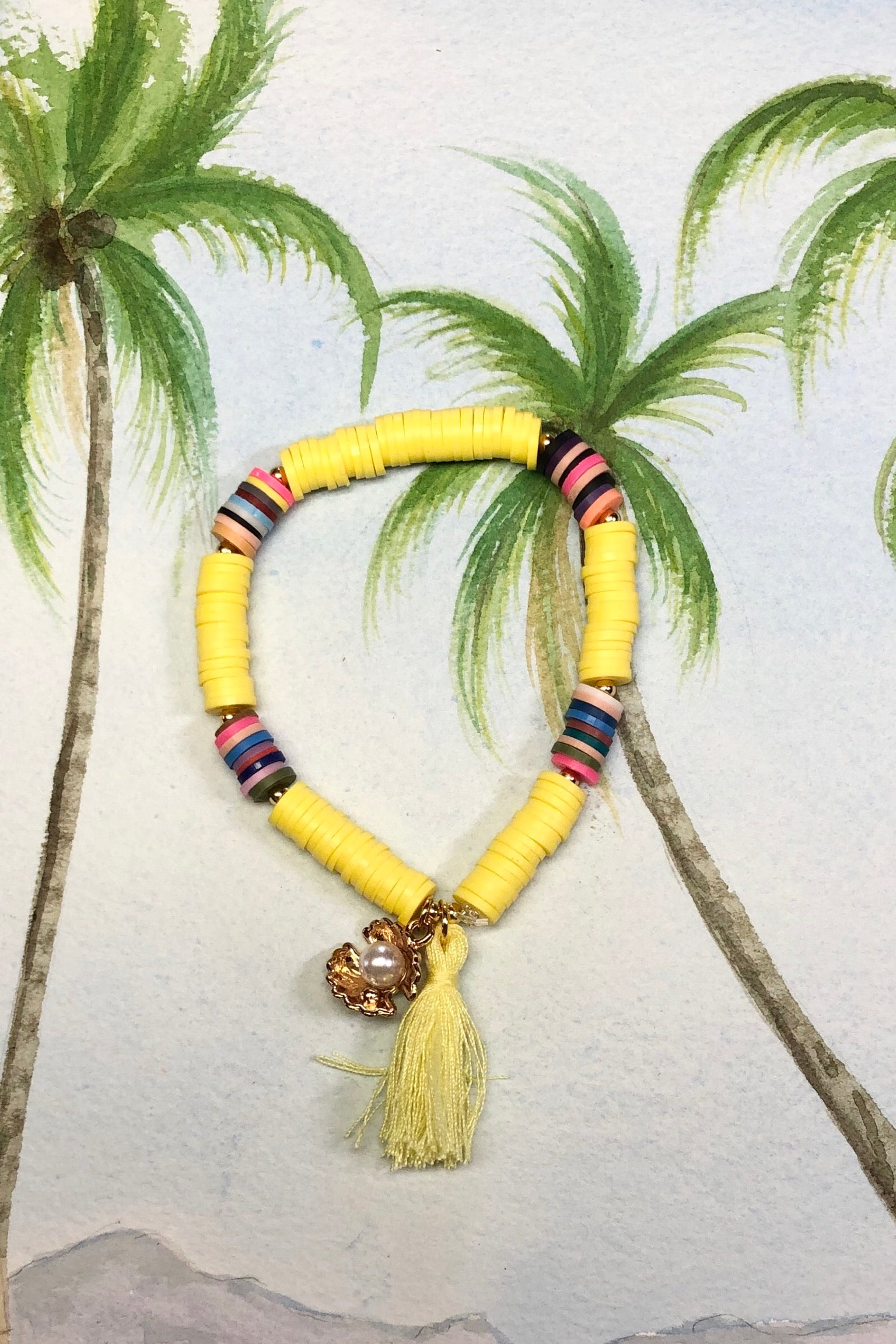 Summer Shell Tassel yelow bracelet has a bright gold coloured sea shell holding a  tiny pearly bead.