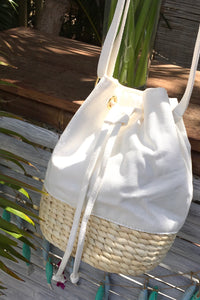 A woven natural straw base with a white canvas drawstring bucket