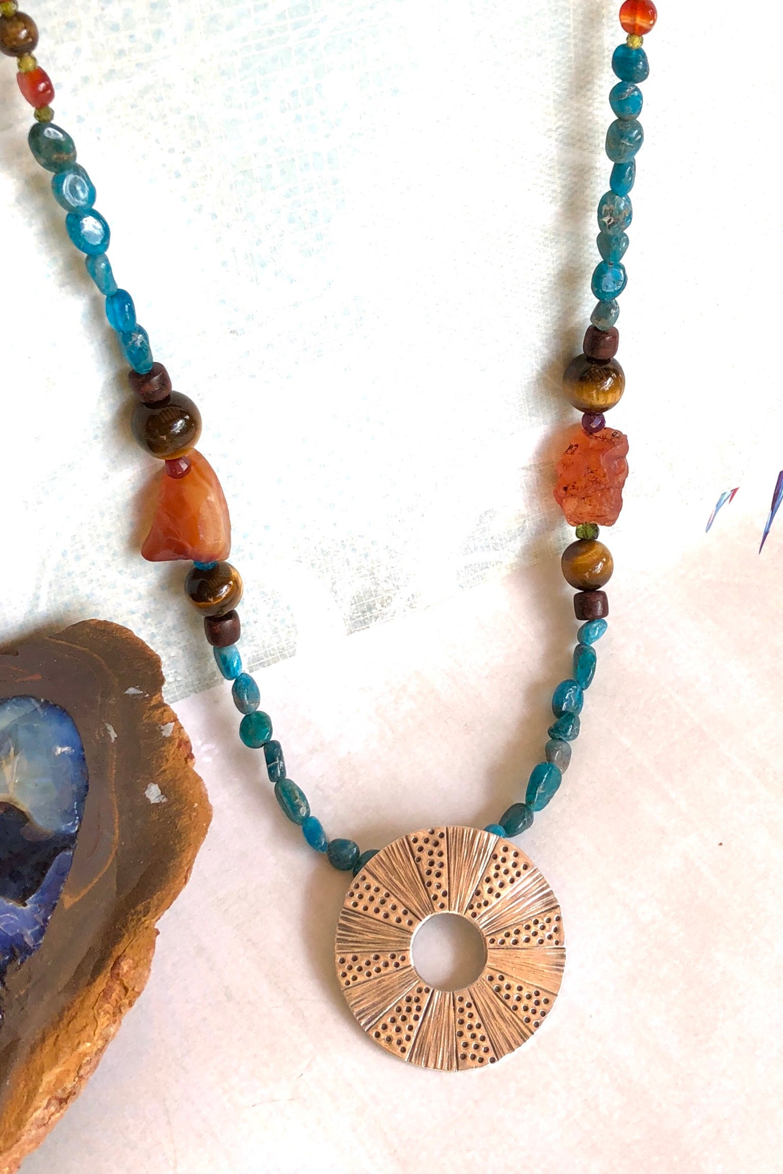 The Necklace Cay Sun Circle and Fluorite is a handmade necklace featuring 54cm in length, natural blue apatite beads, rough chunk of Carnelian and Tigers Eye and wood.