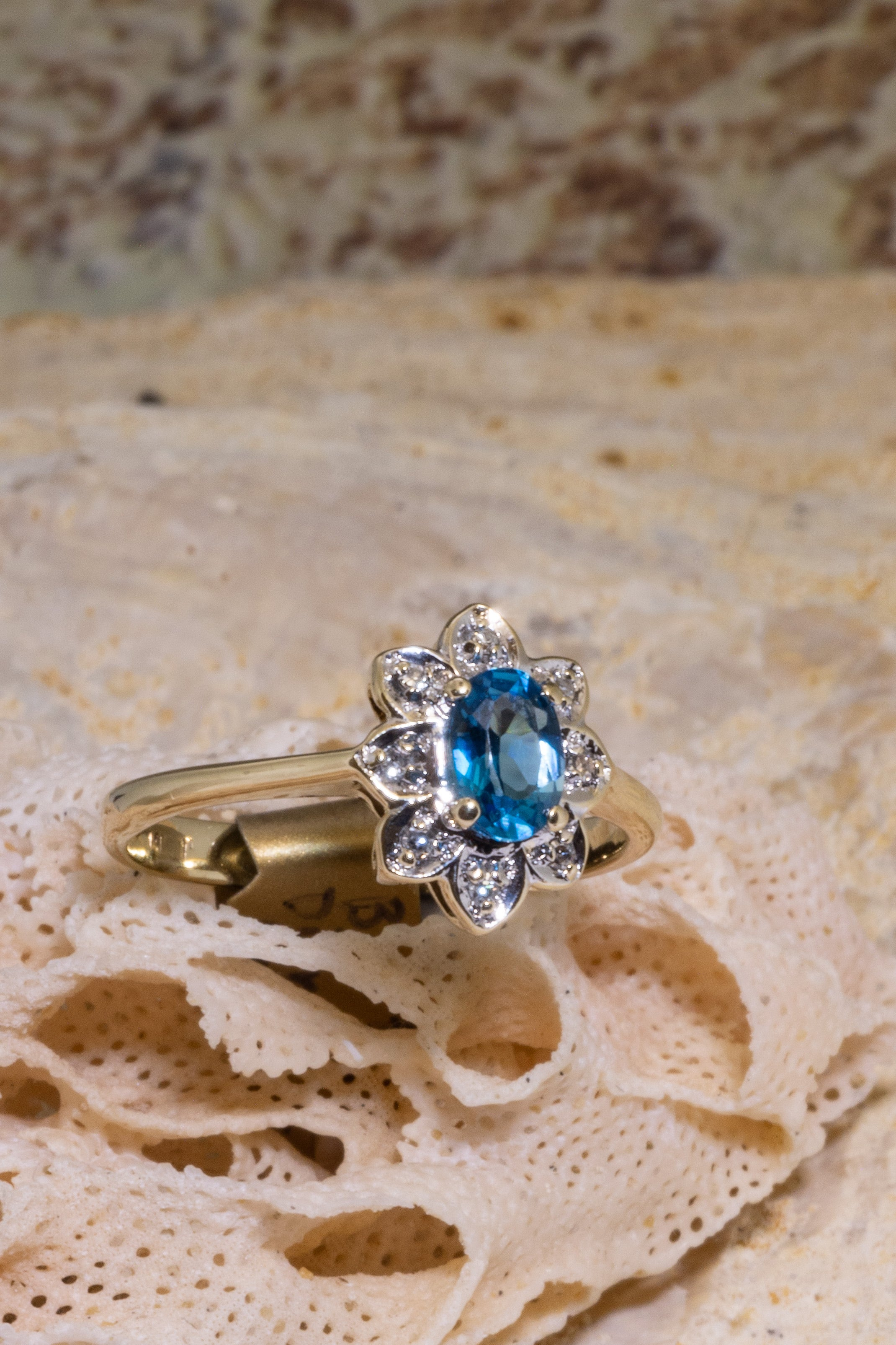Vintage diamond ring features a faceted London Blue Topaz with 8 diamonds in a fancy halo setting