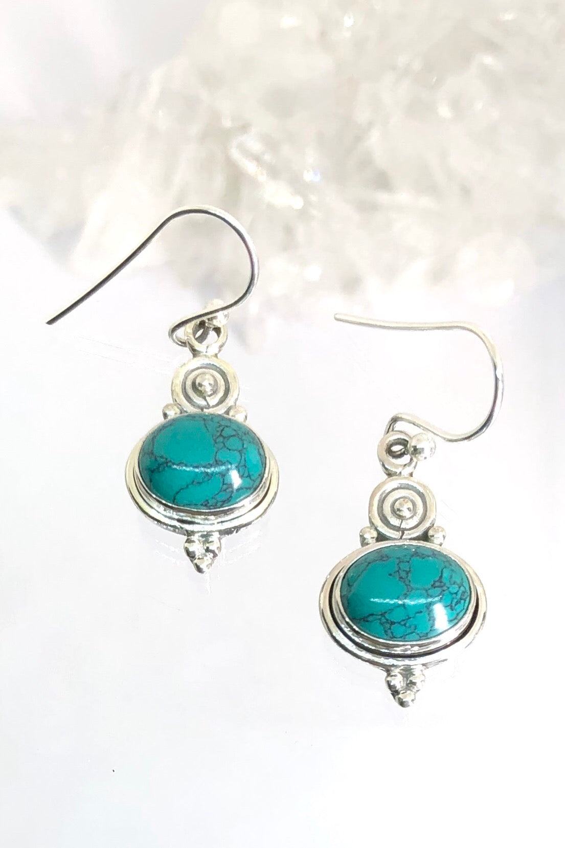 These drop earrings feature a deep-hued gemstone beneath silver swirls.