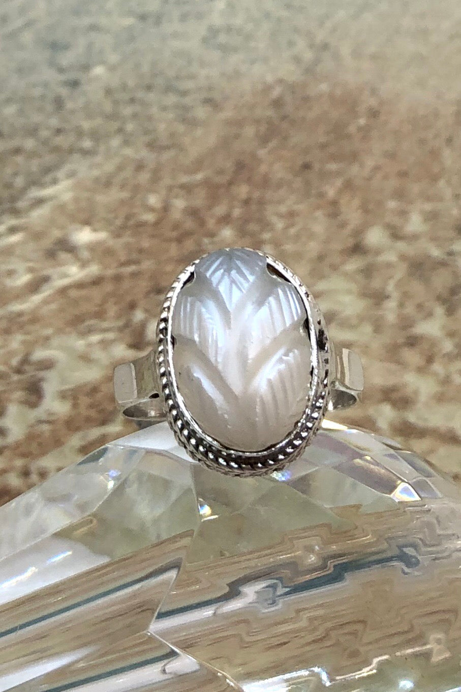 The Echo Ring Moonstone Carving is a handmade moonstone cabachon ring featuring set in silver with a hand carved leaf design.