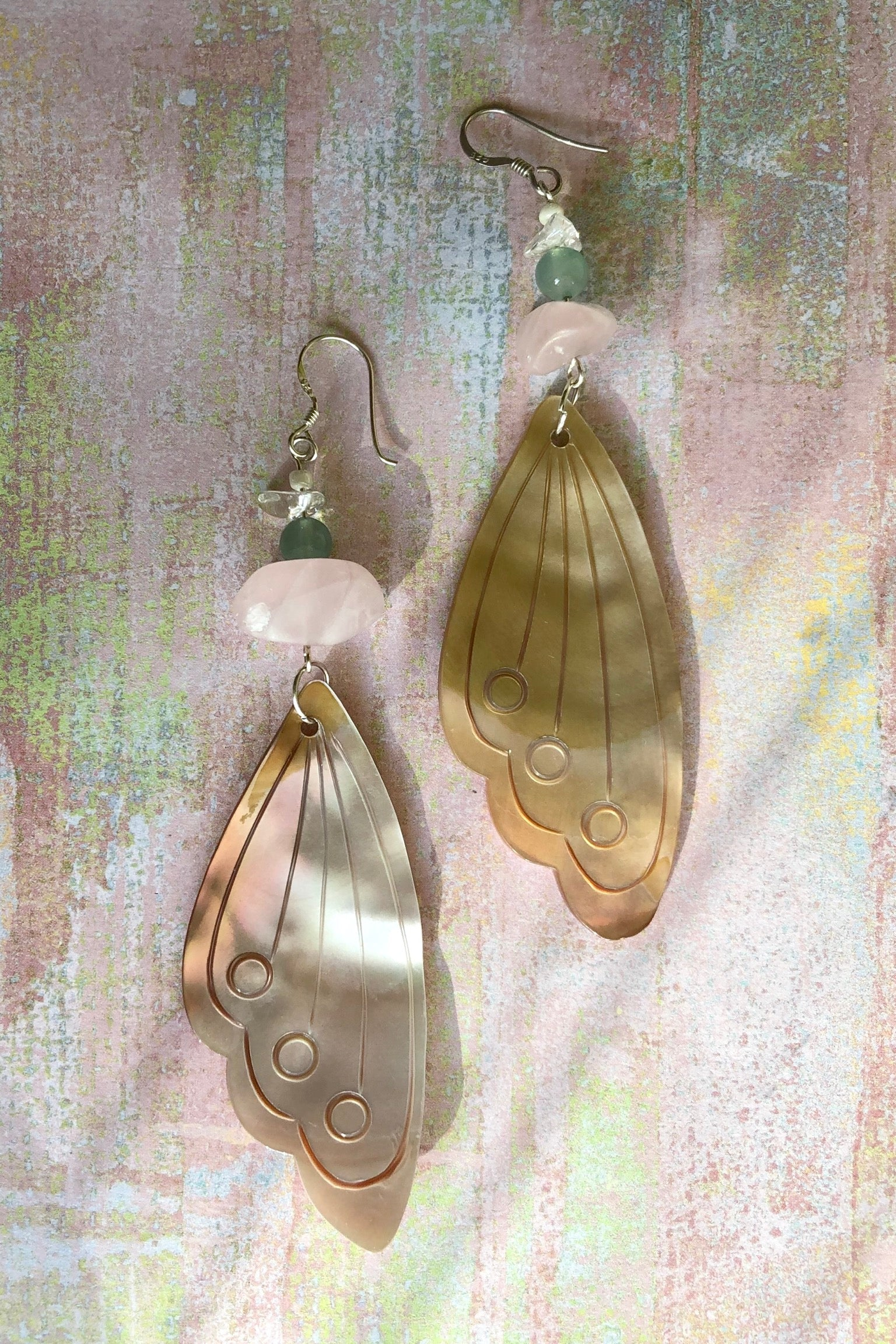 Serendipity Earrings Butterfly Wing Shell Pink are handmade exclusively for us. The gorgeous pale pink Mother of Pearl wing has been hand cut and polished. At the top there is a pebble of natural Rose Quartz, an Amazonite bead and a rock crystal bead.