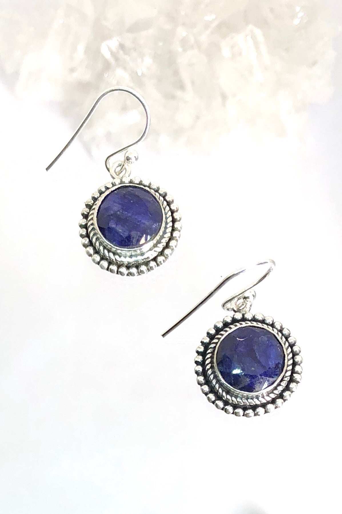 These deep and mysterious earrings feature a dark bezel set gemstone beneath silver swirls