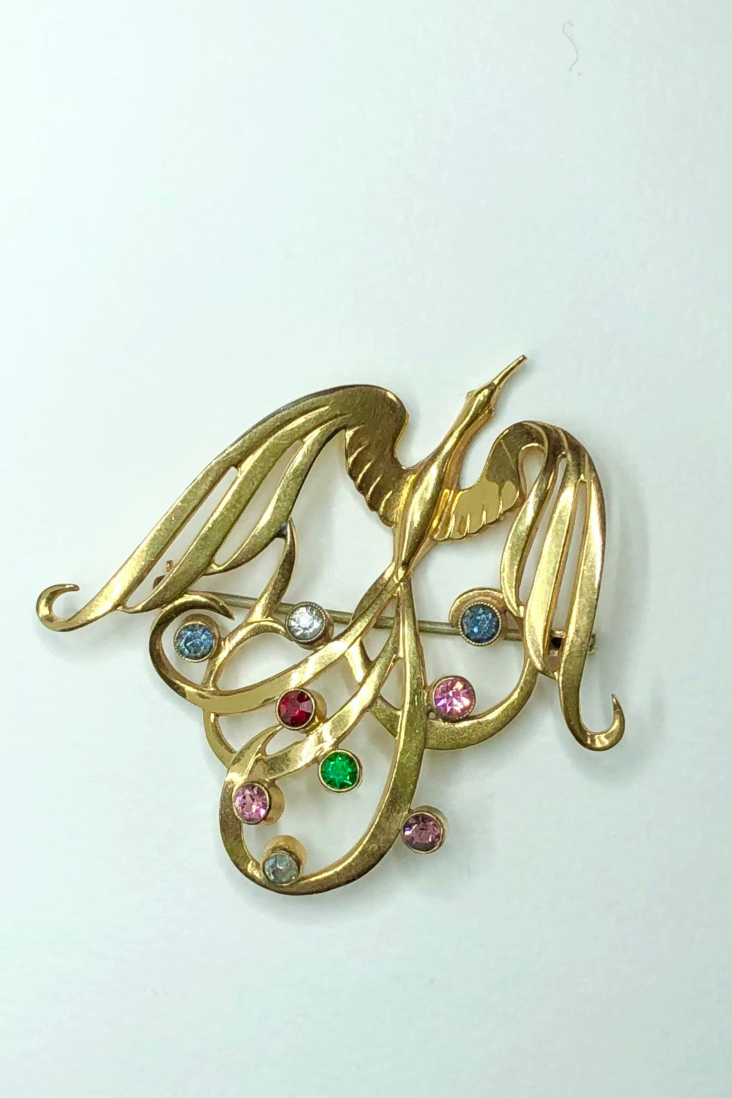 A spectacular jeweled bird brooch, trailing tail feathers adorned with multi coloured crystals. Retro could be 1950's.