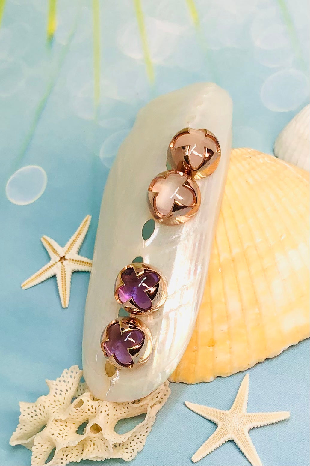 A cabochon dome of gemstone with a daisy pattern surround. Rose Gold vermeil setting.