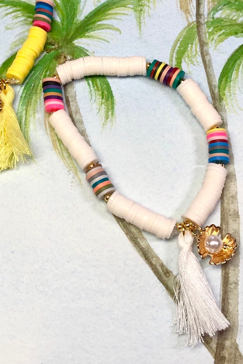 Our Summer Shell Tassel White bracelet has a bright golden sea shell holding a tiny pearly bead. Really cool and island styled.