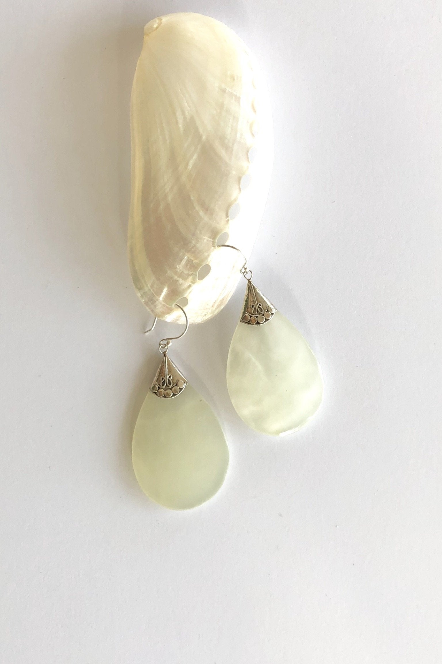 Mother of Pearl teardrop style earrings with 925 solid silver detailing.