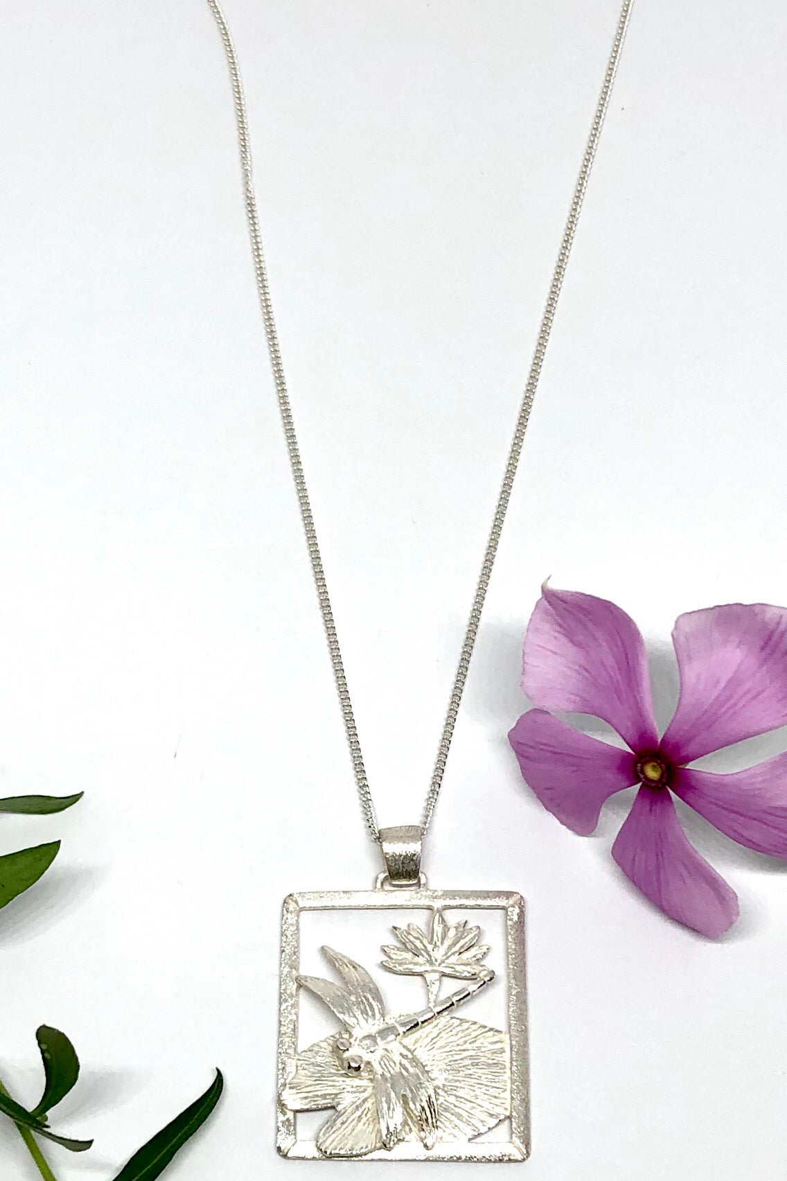The Oracle Pendant Dragonfly is a 925 silver dragonfly on a lotus leaf and a water lily pendant featuring 2.5cm in length and comes on a 925 silver chain.