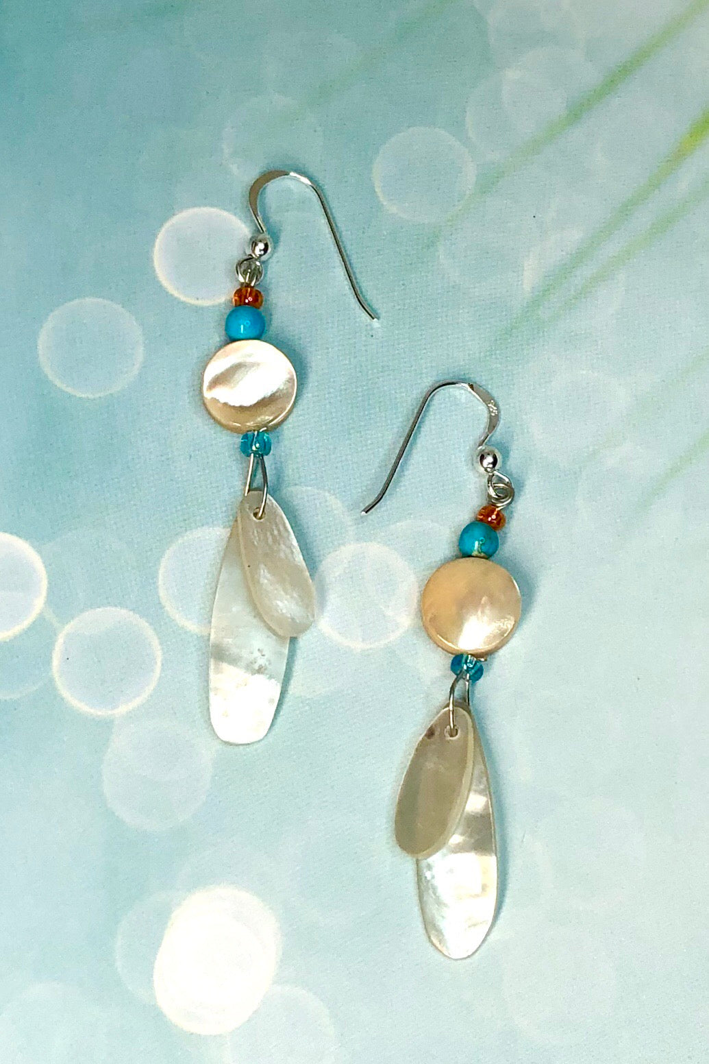 earrings Cay Antika Blue are a sweet little flutter of Mother of pearl shell, topped with a shell bead ans a turquoise Howlite bead. On a 925 silver hook.