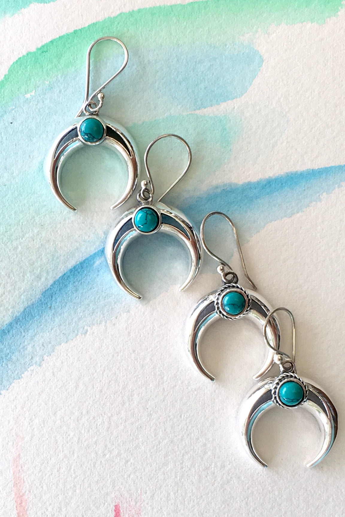 Crescent moon earrings with turquoise bead and detailing. Bohemian design