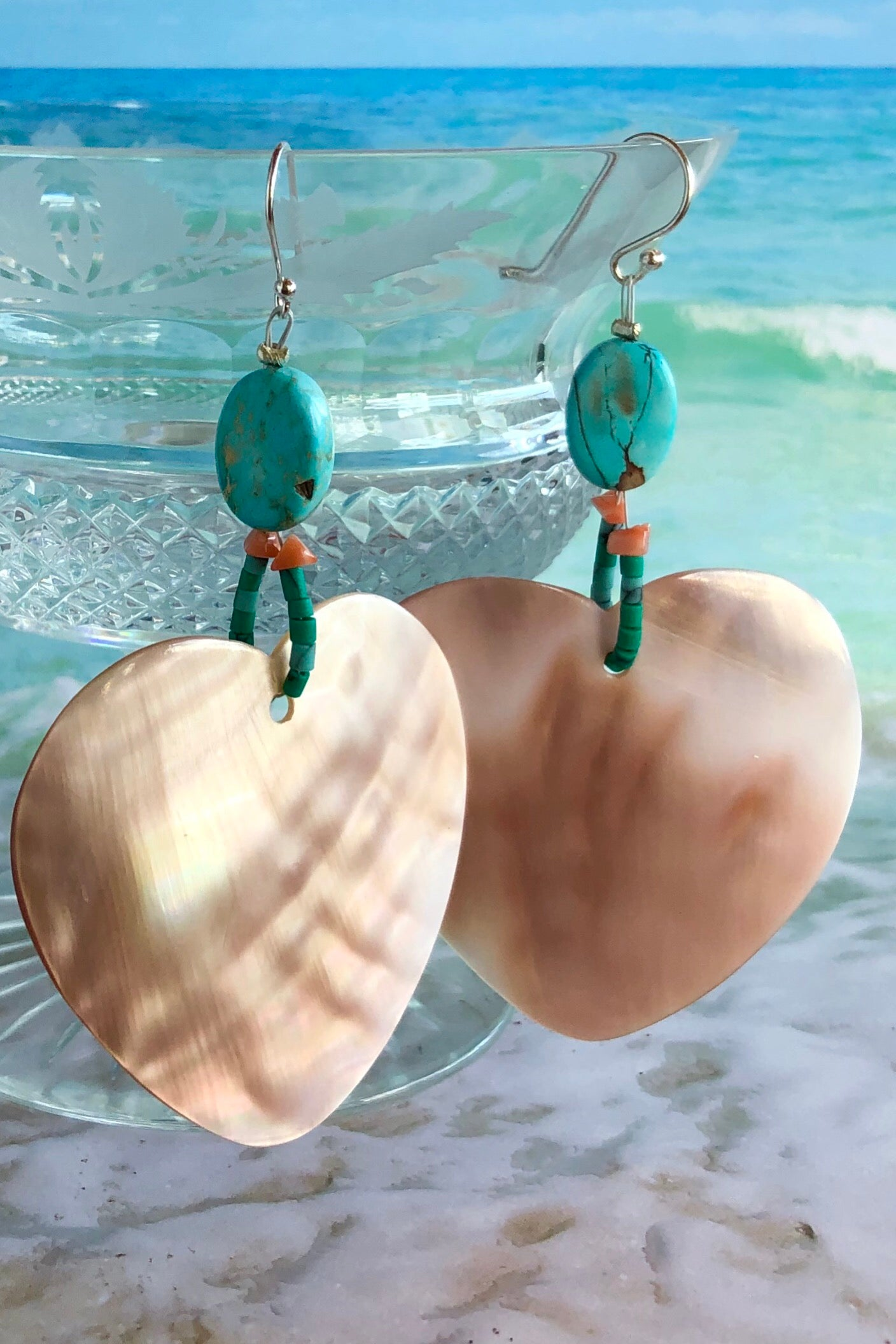 The polished Mother of Pearl shell has been hand cut into a heart shape then polished. The detail is of Turquoise Howlite, pink coral chips and handmade sand beads, the hook is silver.