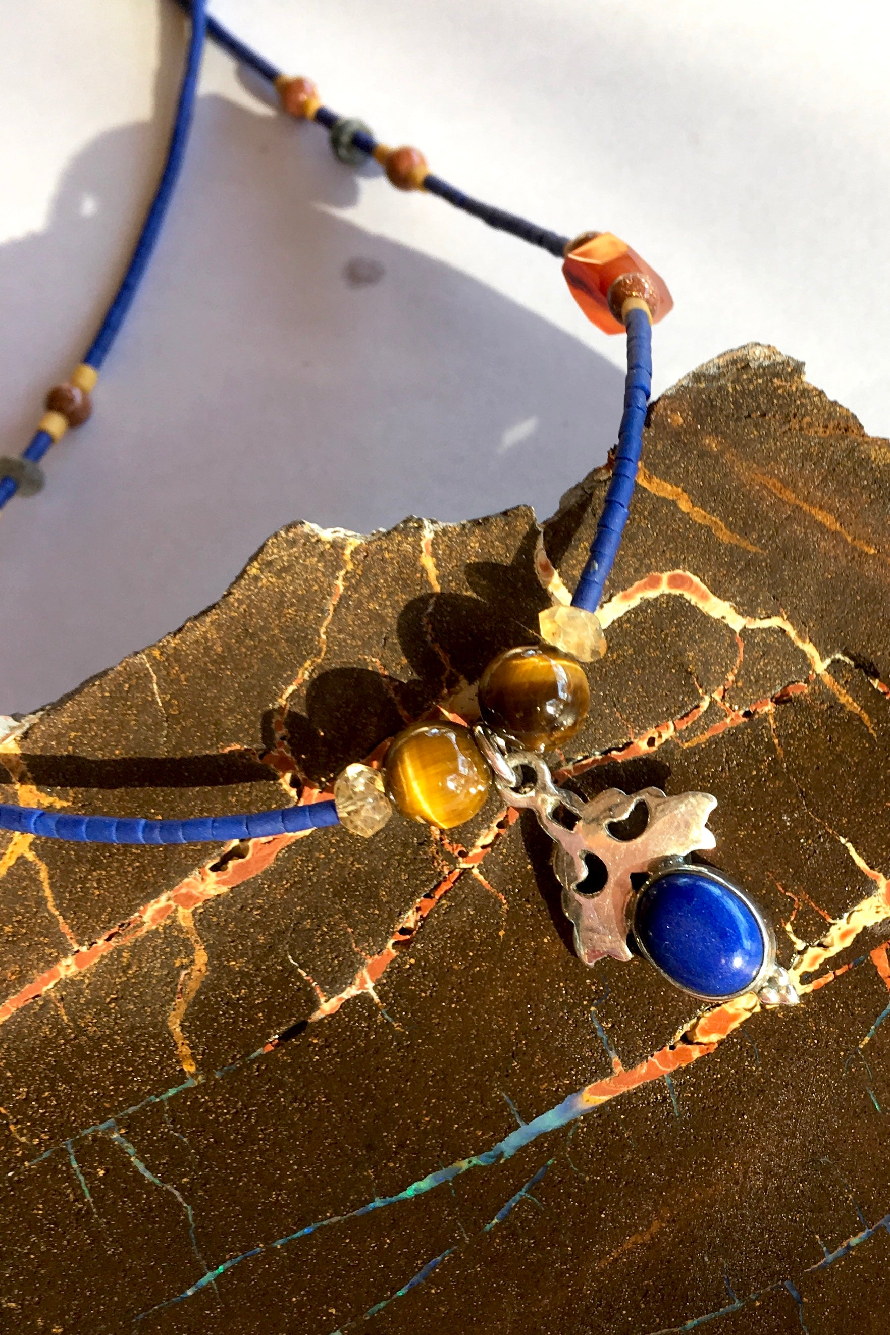 Necklace Cay with Lapis Pendant is 40cm in length with 5 cm extender and Centre piece in 925 silver and lapis lazuli cabachon and beads include Lapis Lazuli, carnelian, tigers eye, faceted semi precious stone and Turkish glass beads.