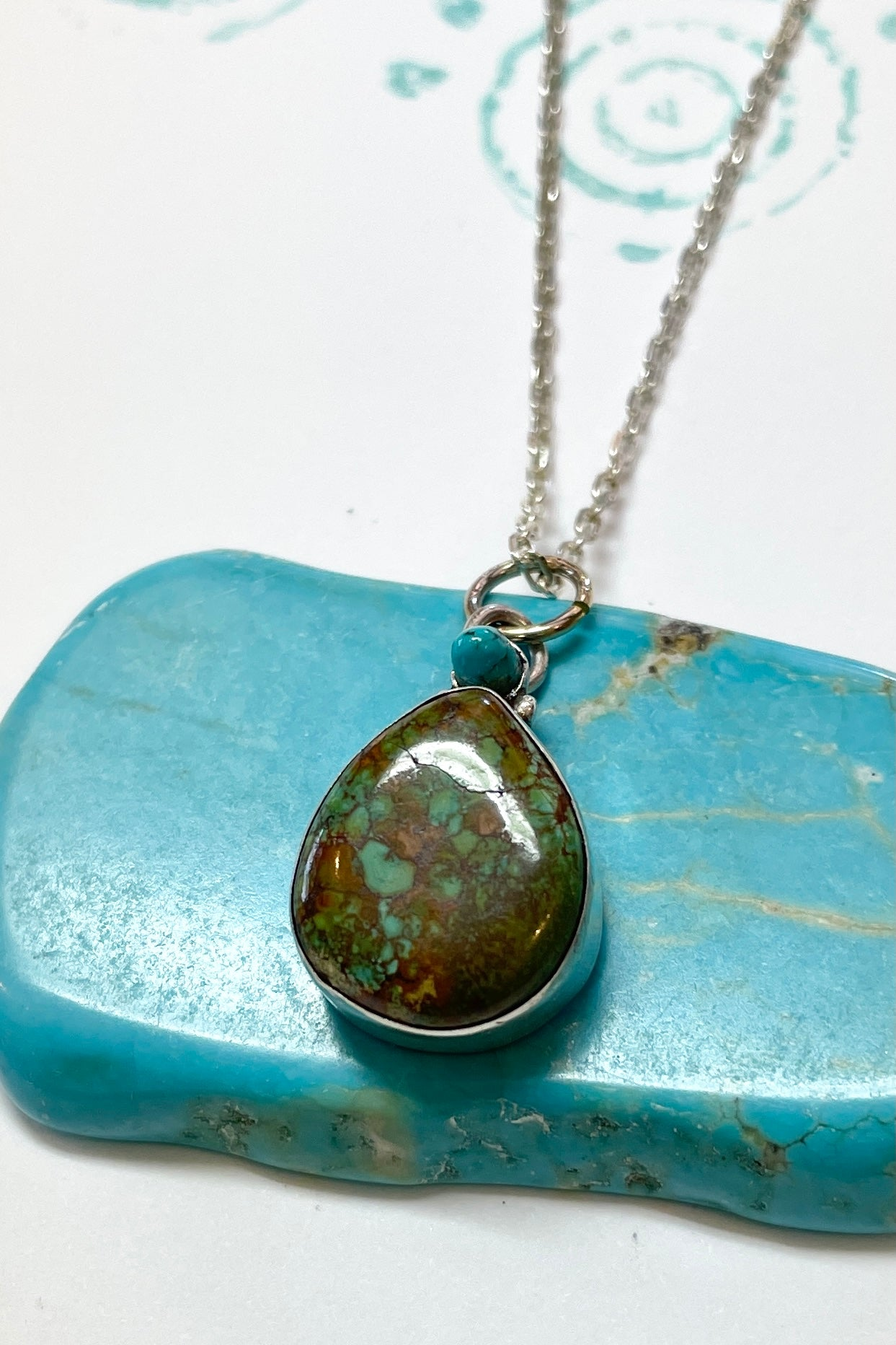 This vintage turquoise pendant has the honest look of a preloved and hand crafted piece. It comes on a silver chain.