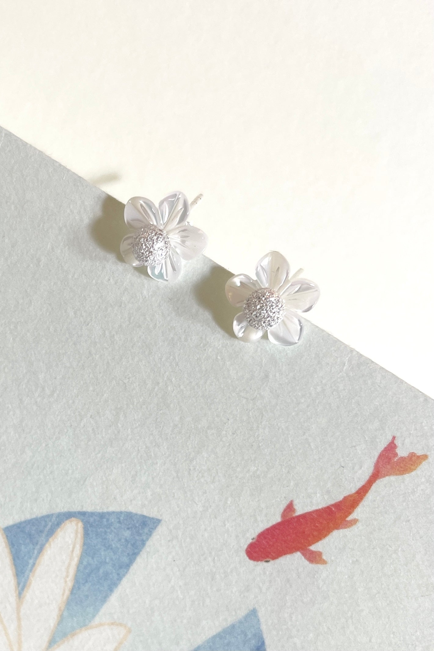 this lovely stud earring is carved from Mother of Pearl, the centre is a tiny silver ball stud that can be worn without the flower.