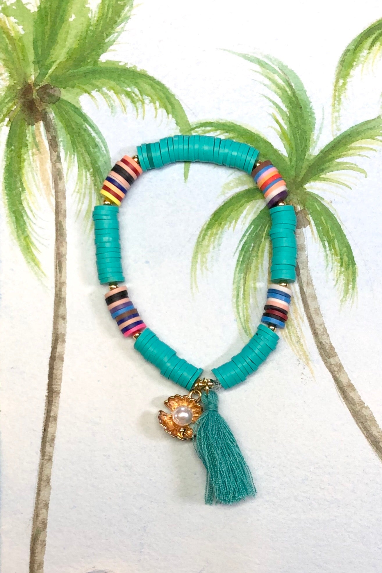 Summer Shell Tassel teal bracelet which has a bright golden sea shell holding a tiny pearly bead.