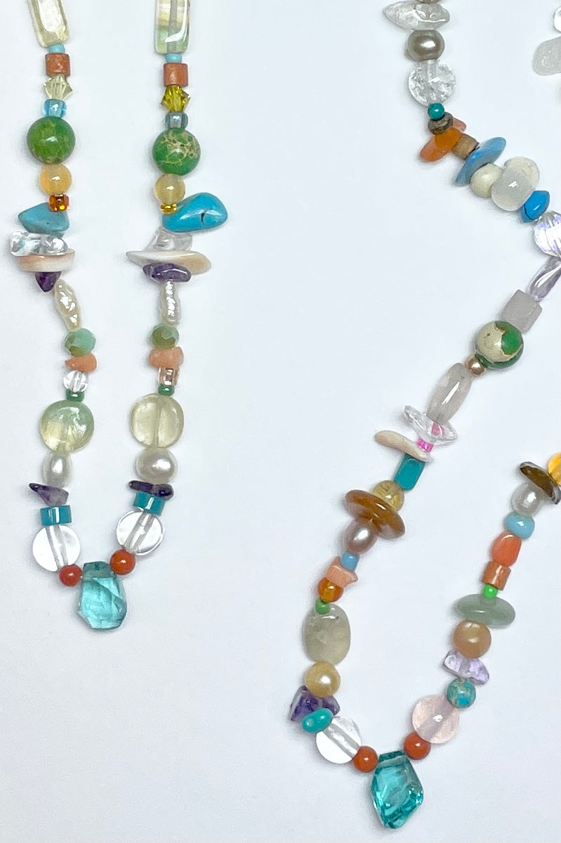 "Our necklace Cay Precious is a sweet choker style hand made using random choice of gemstones, crystal, glass and shell beads in subtle mix of pretty colours. The centrepiece is a tiny bright turquoise apatite ""Geo Cut"" stone."