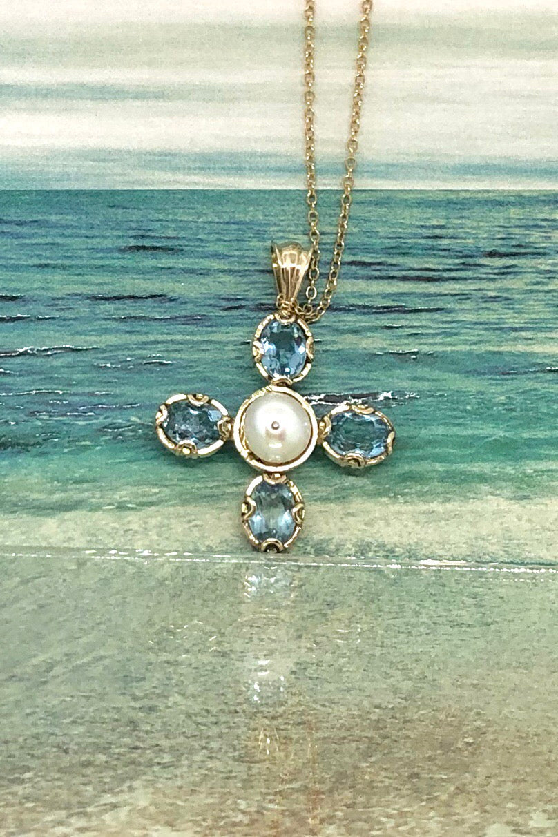 A stunning star shaped pendant with four blue topaz stones set around a white pearl