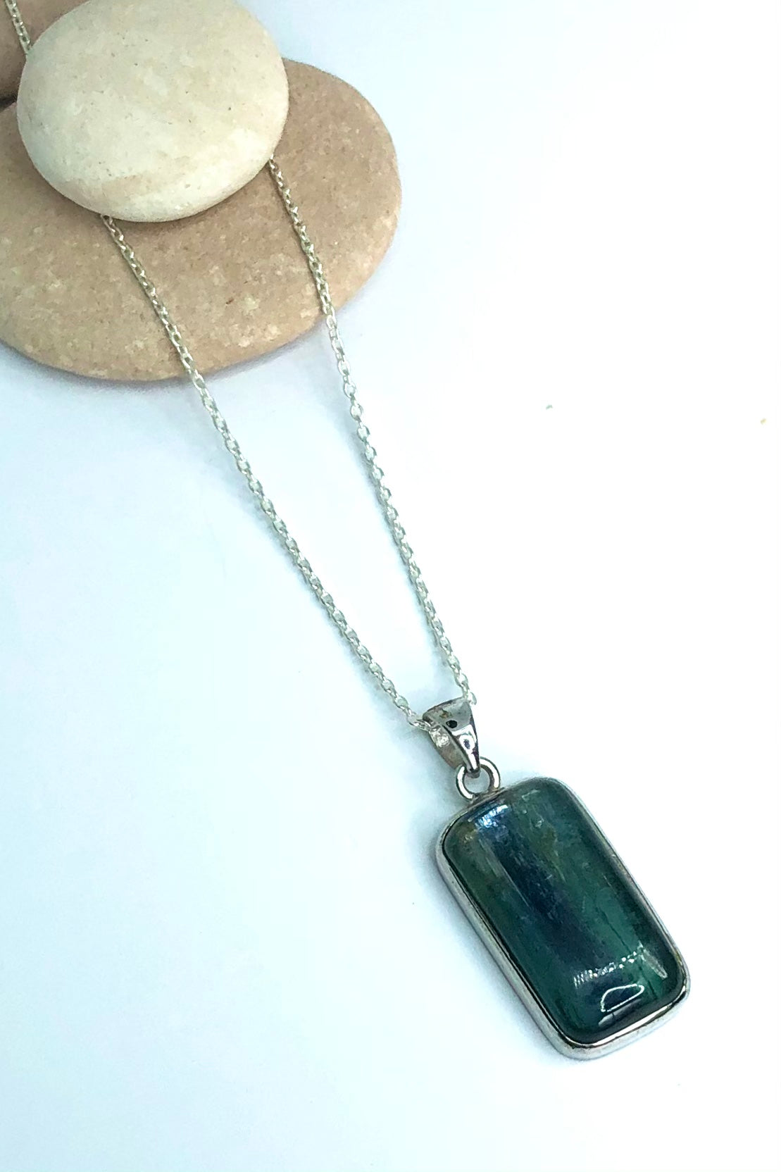 This stone is dark blue green throughout, with a stronger grey blue down the middle, and silvery flashes. It is  blue grey when held to the light, cut to a high dome rectangle cabochon.