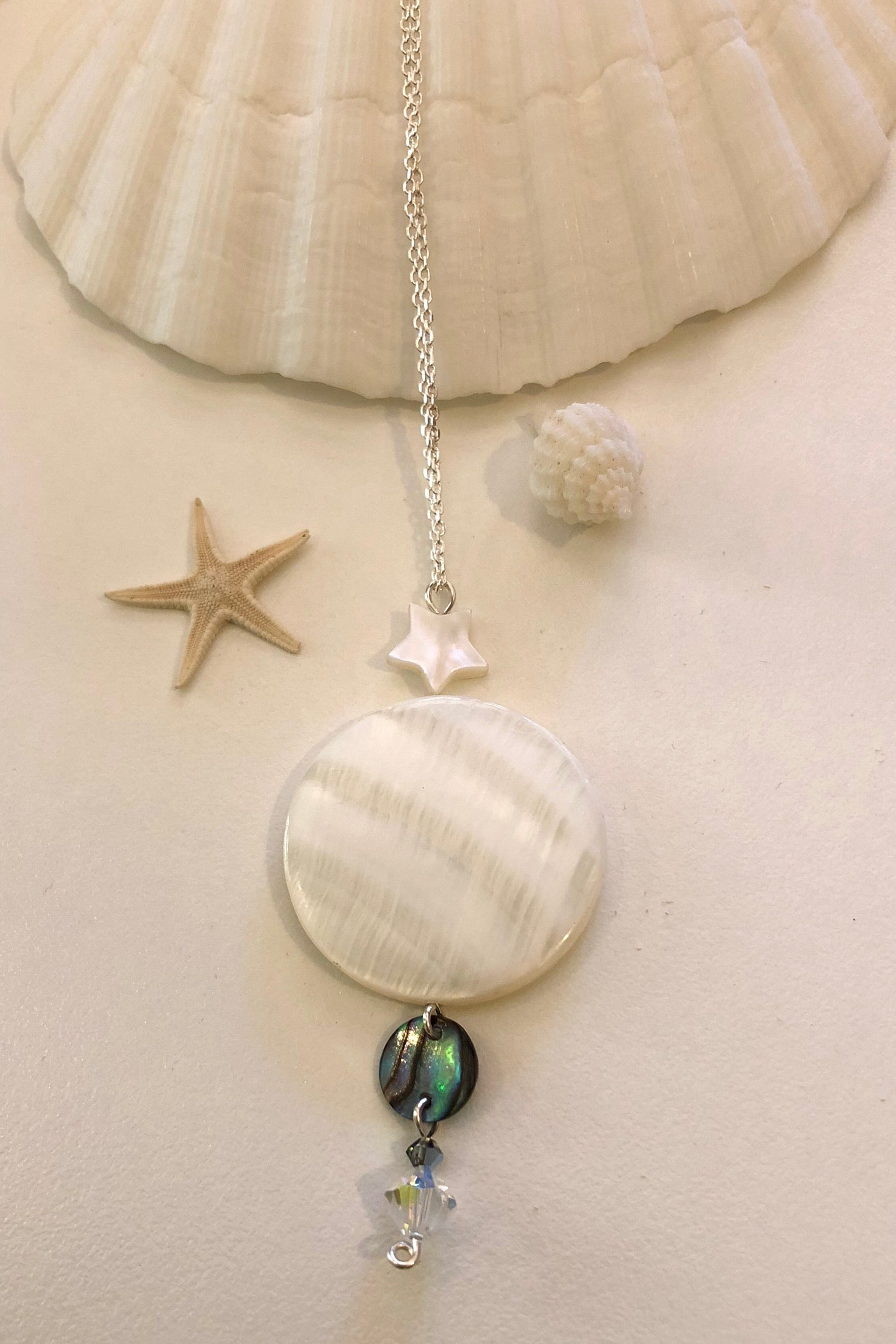 This pure and lovey mother of pearl disc has a beautiful under the sea glow, and is polished to a high shine, it hangs from a white shell star, and has a highlight of paua shell.