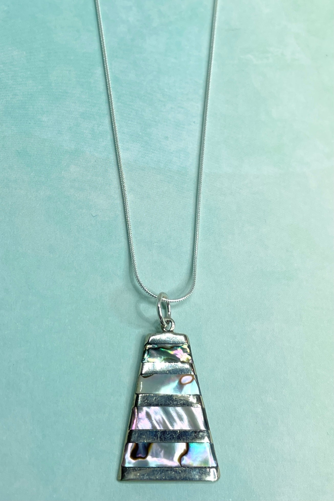A lovely use of the mystical Paua shell in this unusual triangular pendant, set in silver.