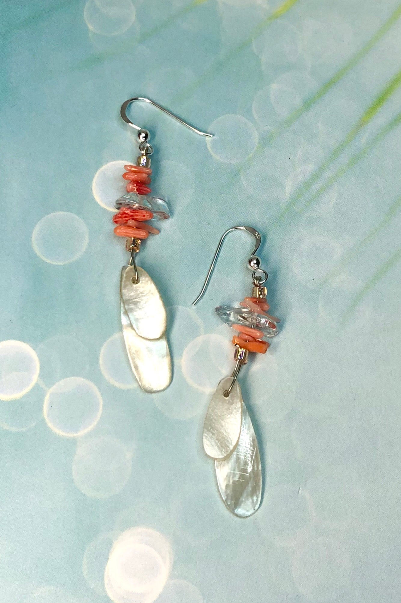 These earrings Cay Antika Coral are a sweet little flutter of Mother of pearl shell, topped with tiny coral and rock crystal beads. On a 925 silver hook.