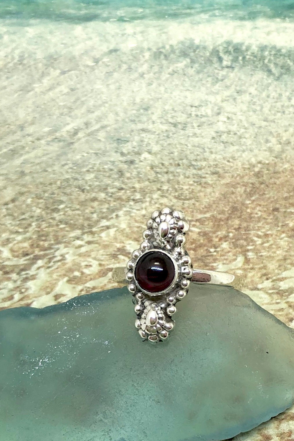 The Echo Garnet Flora is set in 925 silver in a traditional Tibetan style leaf design with garnet and handmade in Tibet.