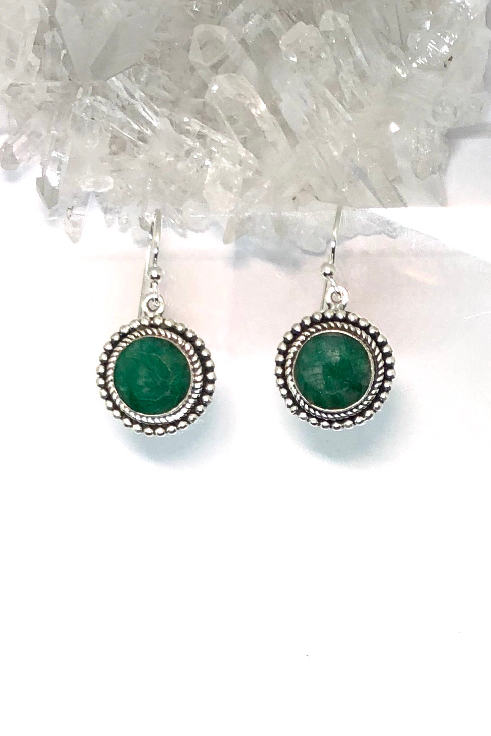 A gorgeous green emerald sits at the centre of silver petals on these earrings