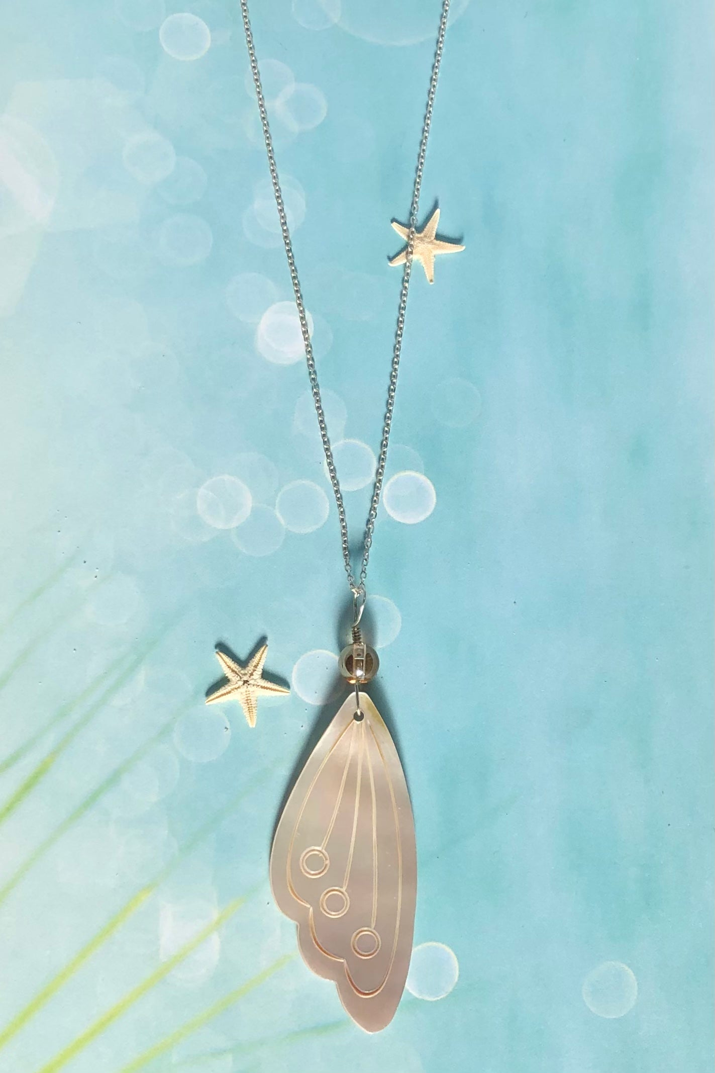 The delicate butterfly wing in gold and silvery bronze Mother of Pearl has been hand cut and polished. At the top there is an iridescent crystal bead.