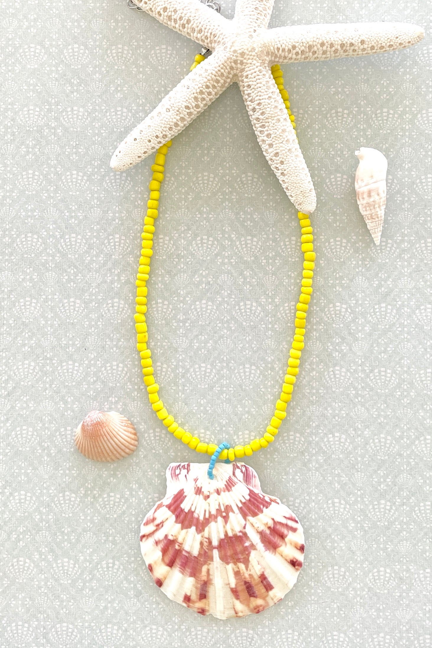 these collected sea shells all carry different patterns, no two ever alike and you can swim in this necklace! its strung on the brightest happy glass beads.
