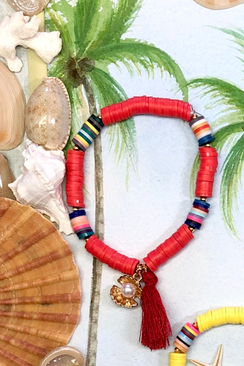 Shell Tassel Red bracelet has a bright gold coloured sea shell holding a  tiny pearly bead.
