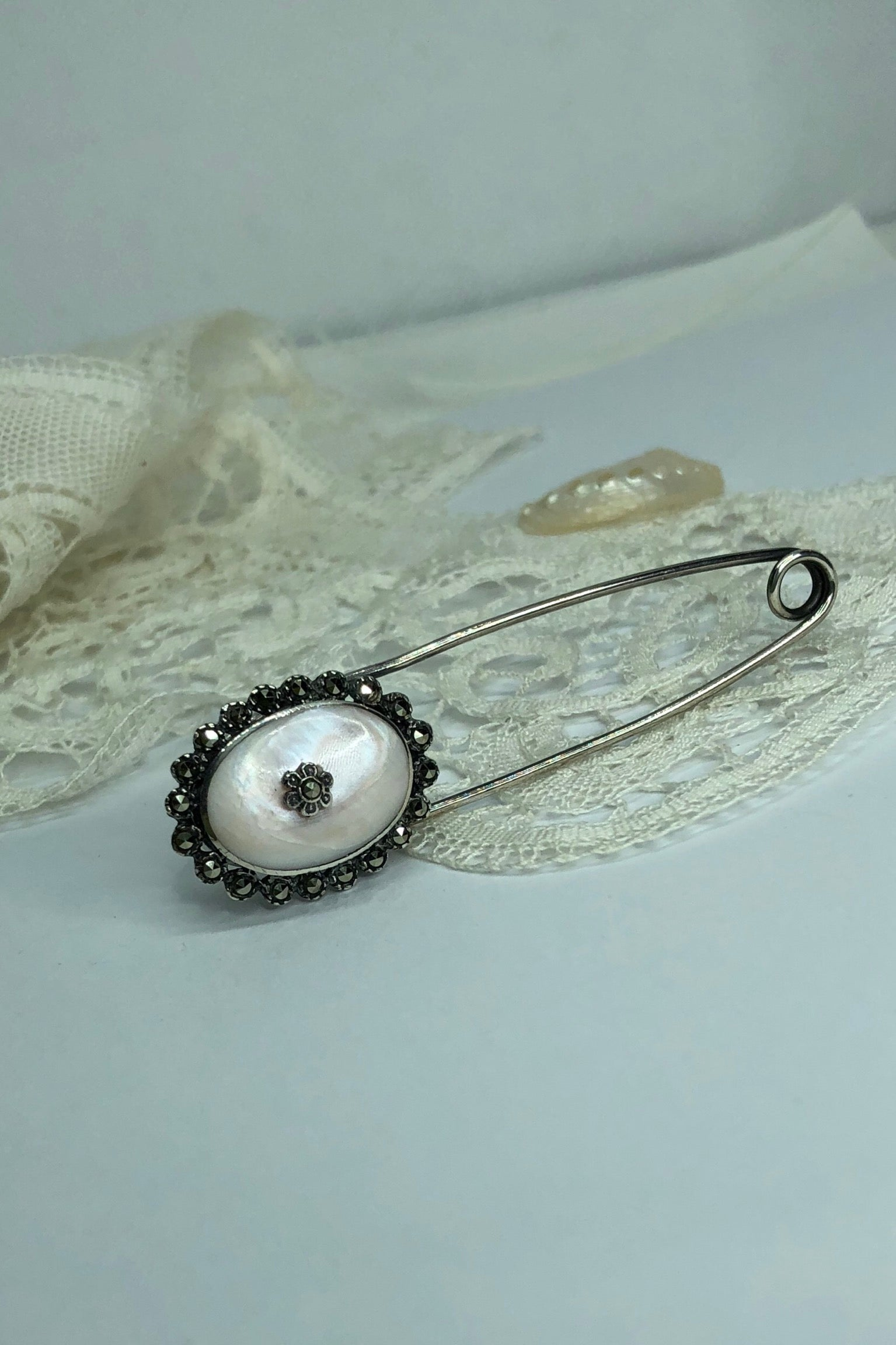 A vintage safety pin brooch with pink Mother of Pearl and Sparkly marcasite. Can be used as a Kilt pin.