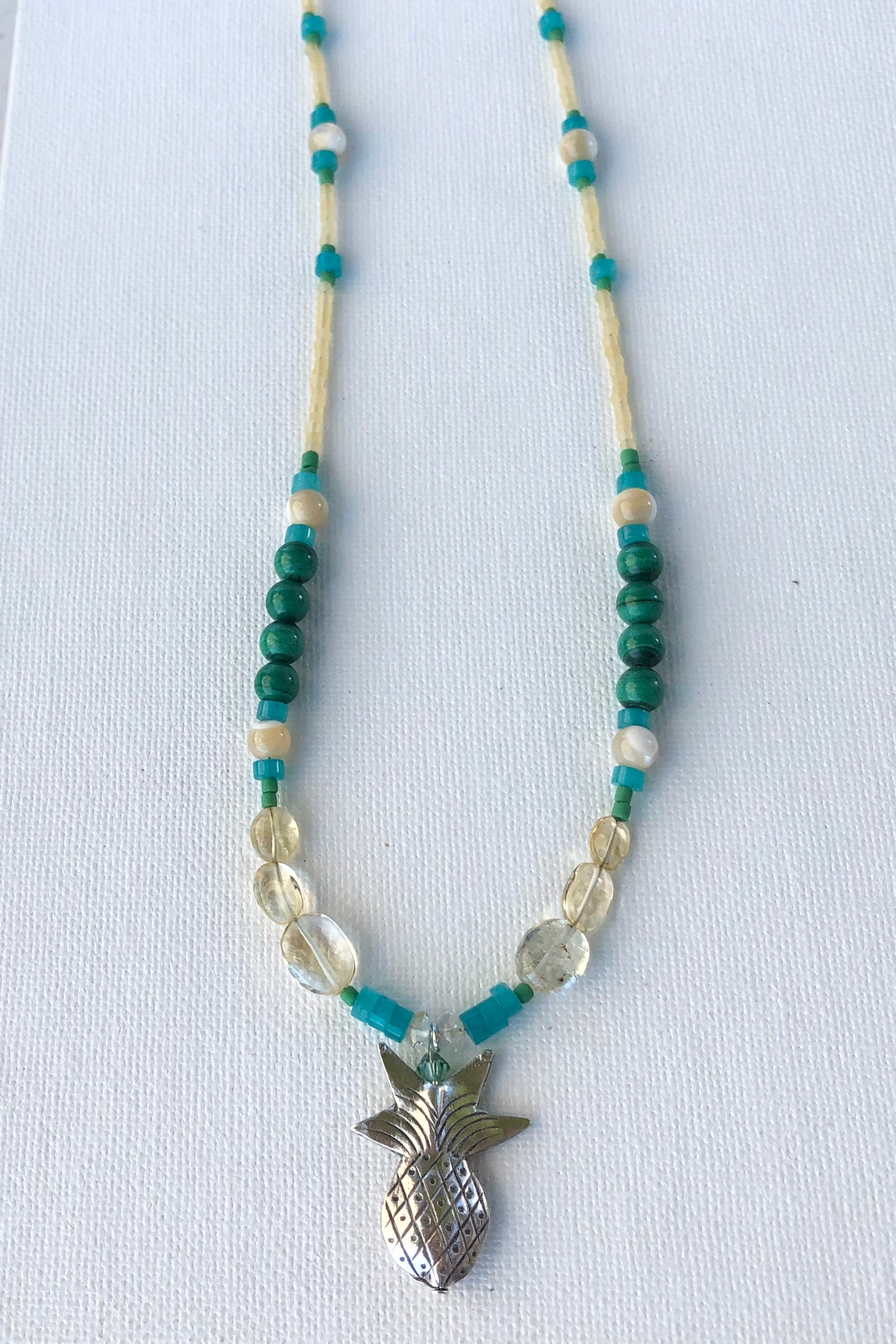 This necklace Sunny Coast inspired one off piece was made in our Noosa Studio,  There is a Thai silver pineapple as the central focus, the beads are the green, gold and turquoise of the area.
