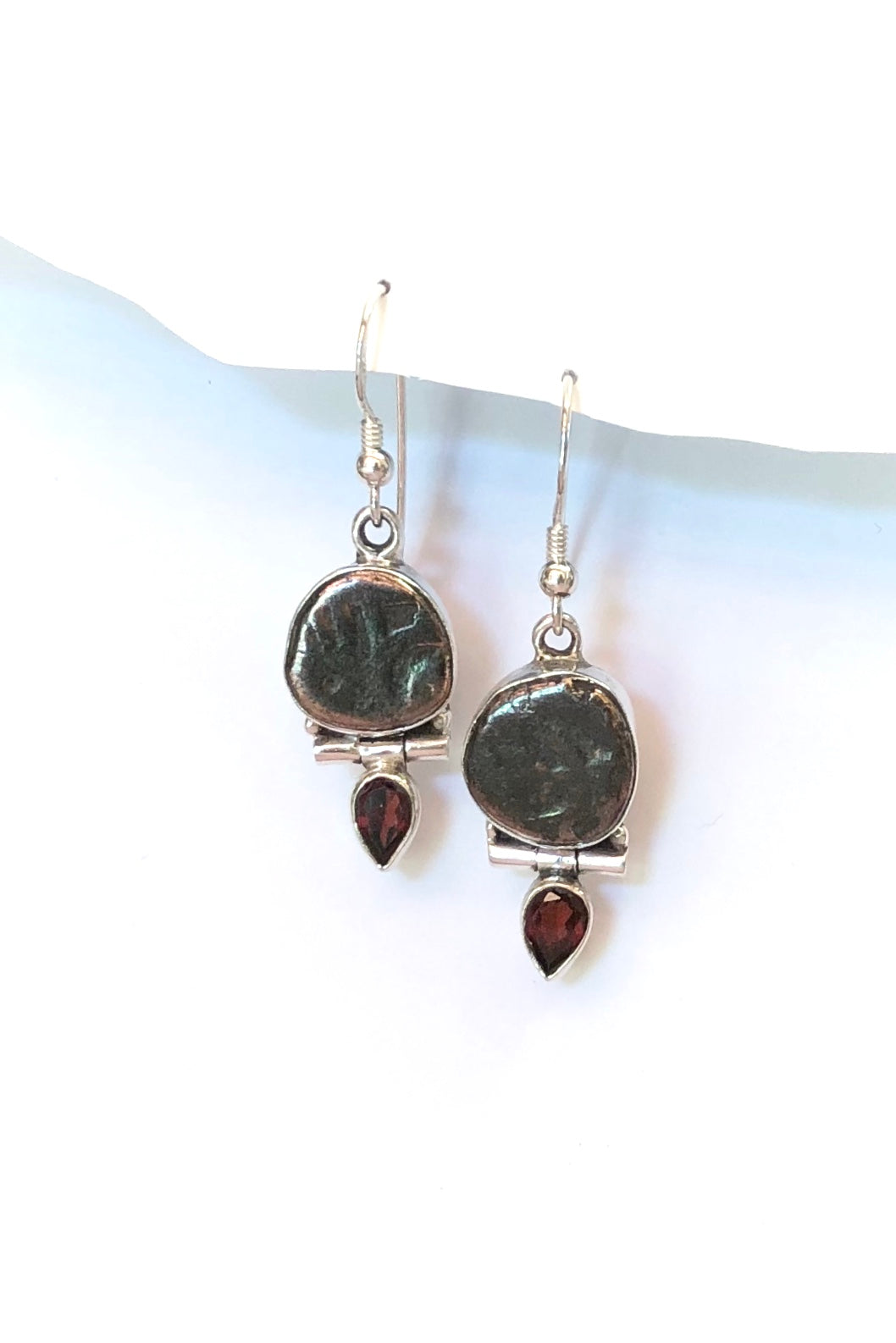 The Echo Earrings Ancient Imprint are 925 silver earrings featuring a metal coin shaped token that has been imprinted with a symbol and pear shaped red garnet gemstone.