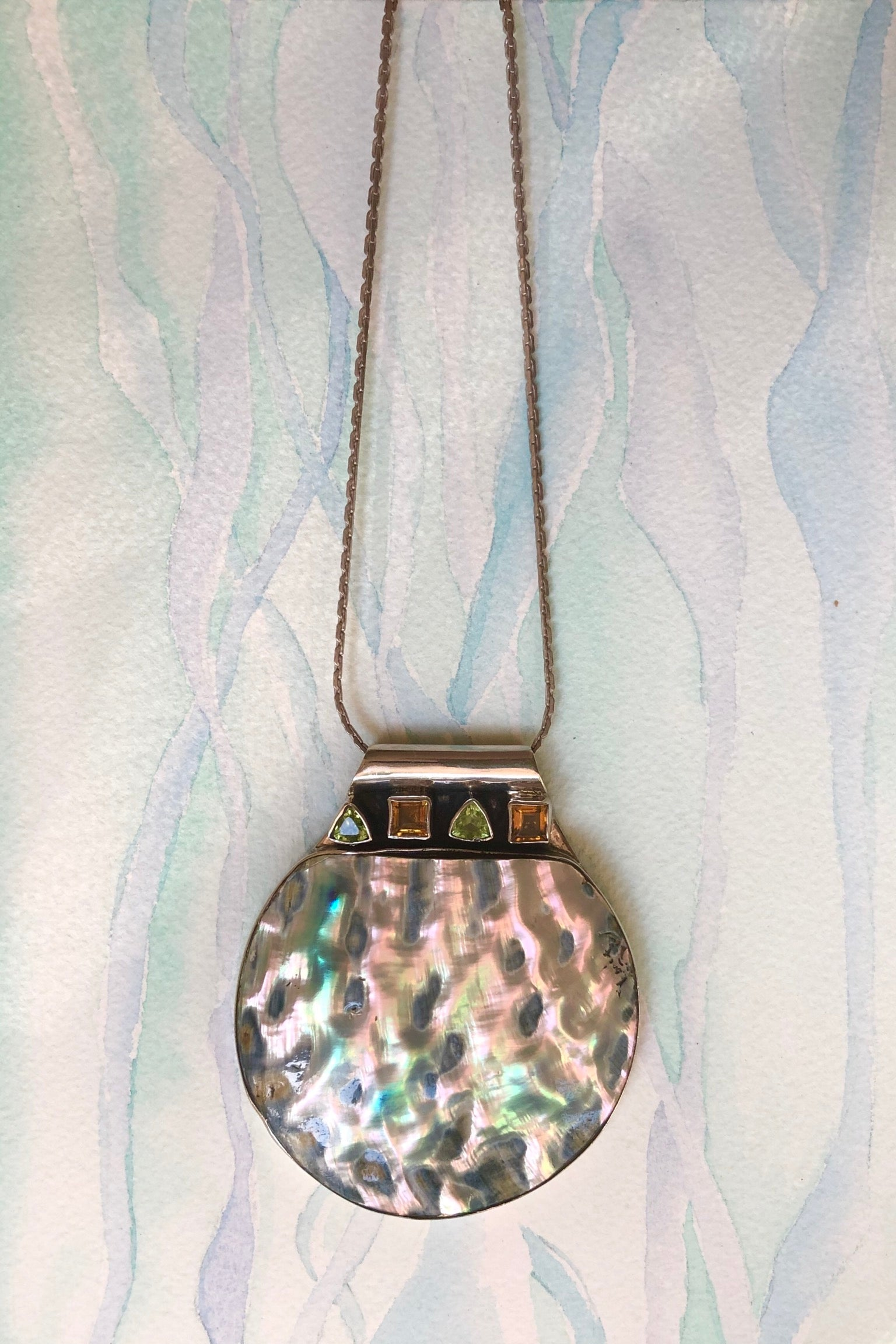 Echo Sea shell and Gemstone Silver Pendant is cut from a gorgeous shimmery shell with citrine and peridot gemstones along the top. This comes on a silver chain.