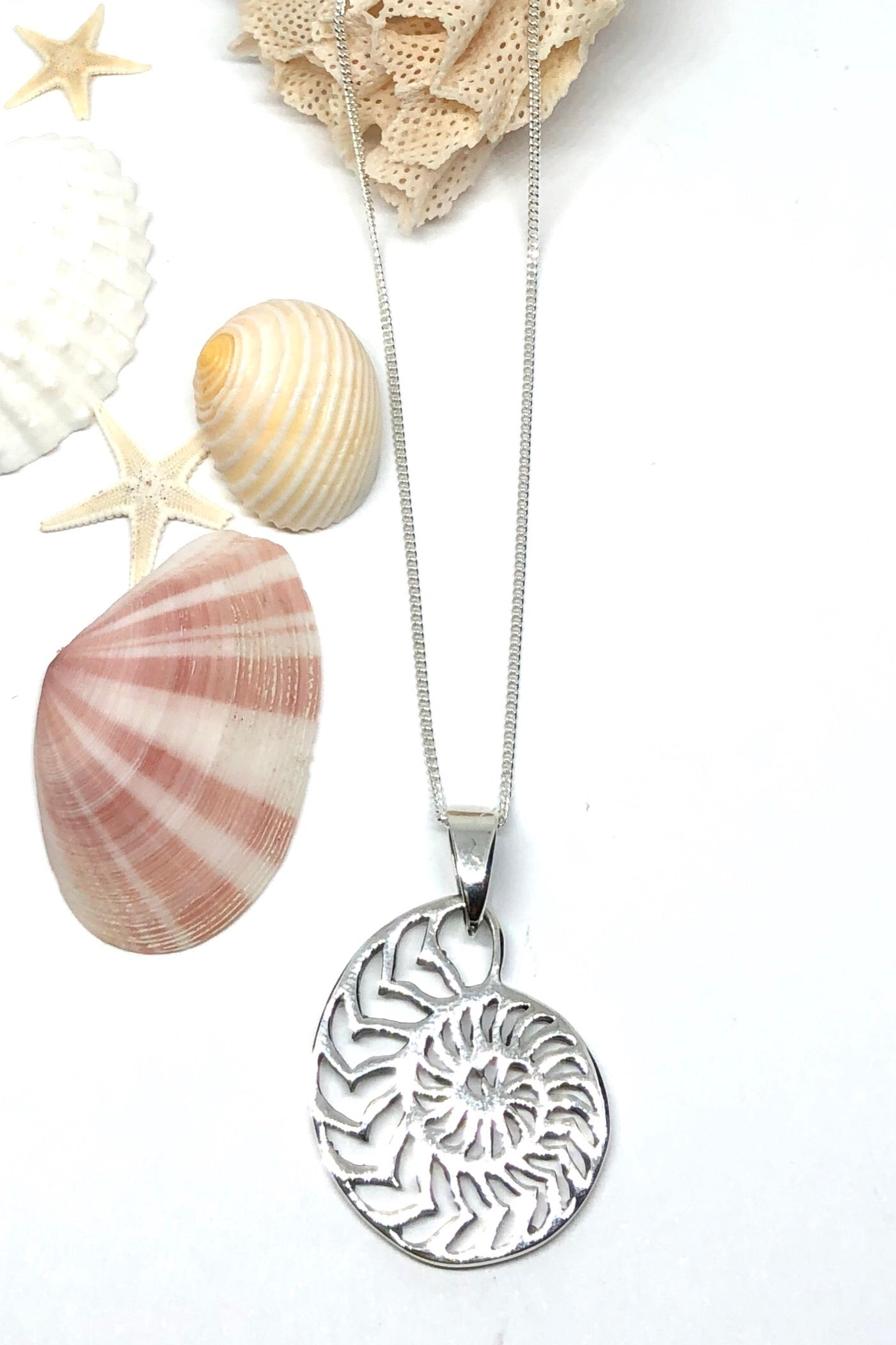 A swirl of the gorgeous nautilus shell shape, this silver pendant is the ocean necklace of dreams
