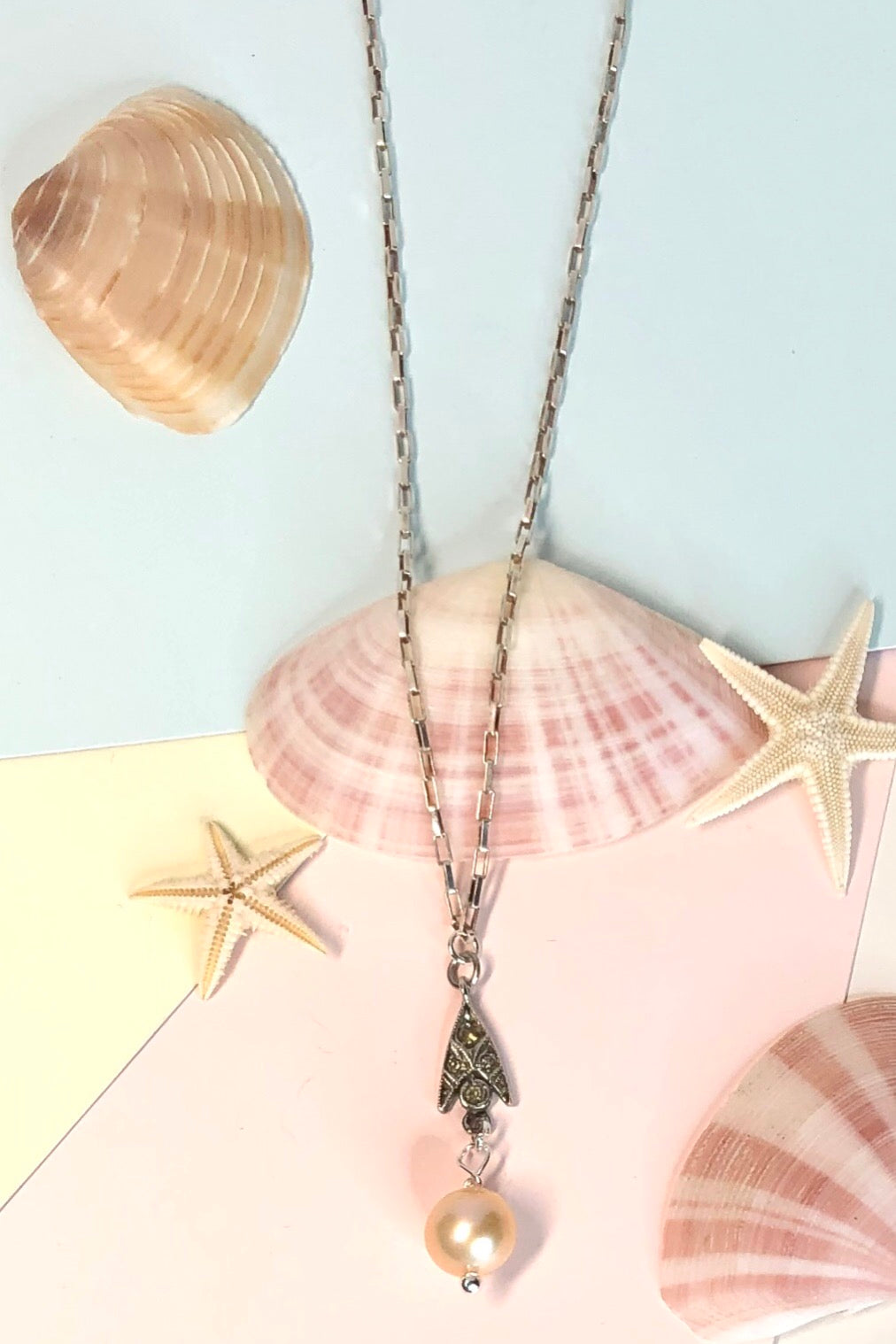 The Echo Pearl Droplet Pendant has silvery and paste detail and  pink pearl hangs from base.