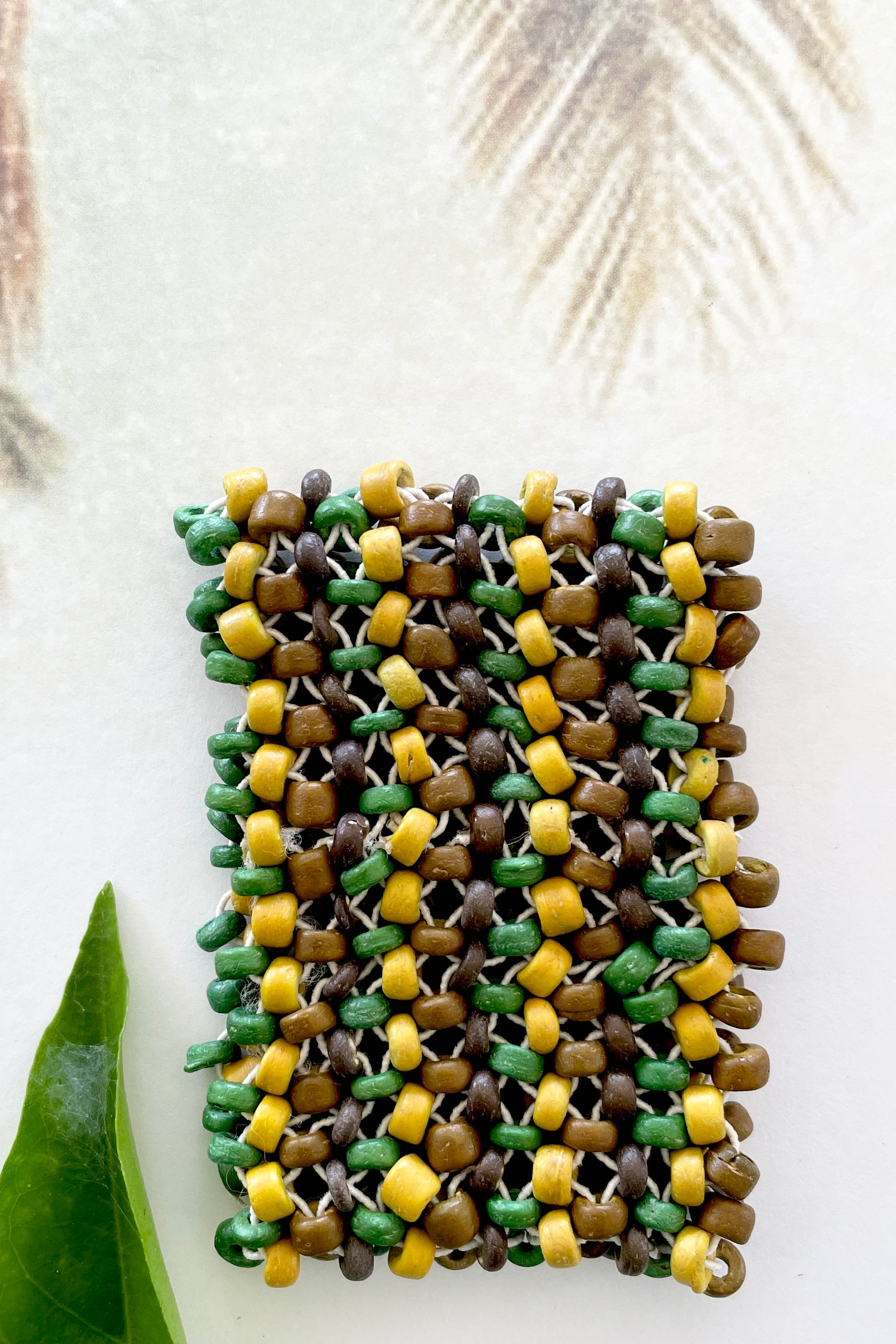Simple and soft, a woodland style with hand cut wood beads in shades of green.